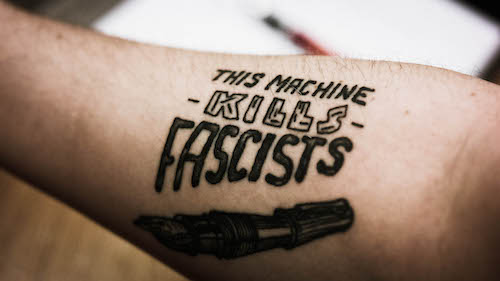 """A photograph of a forearm tattoo, in black ink with the words 'This Machine Kills Fascists' above a fountain pen."""